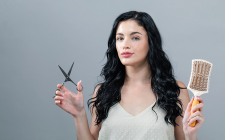 Woman cutting her hair with scissors on a gray background Banco de Imagens