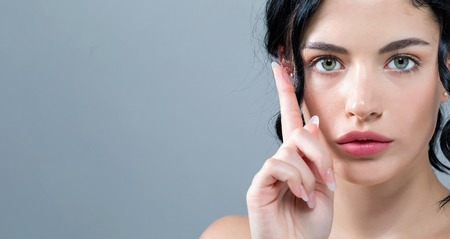 Junge Frau mit Kontaktlinsen auf einem grauen Hintergrund