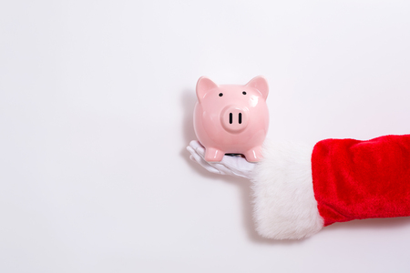 Santa claus holding a piggy bank on a white background