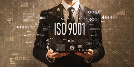 ISO 9001 mit Geschäftsmann, der einen Tablet-Computer auf einem dunklen Weinlesehintergrund hält