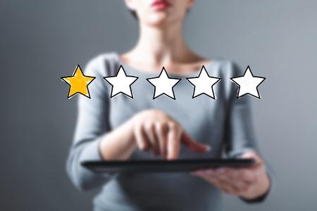 Eine Sternebewertung mit Geschäftsfrau, die einen Tablet-Computer verwendet Standard-Bild