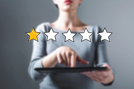 One star rating with business woman using a tablet computer Banco de Imagens
