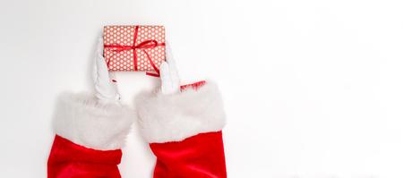 Santa sosteniendo un regalo de Navidad sobre un fondo blanco. Foto de archivo