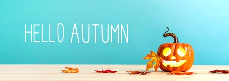 Hello Autumn message with pumpkin with leaves on a blue background Stock Photo