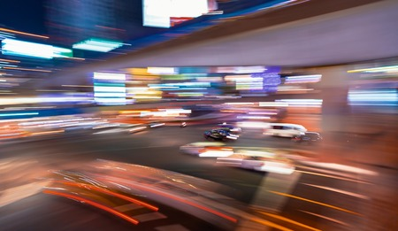 Abstract blurred view of people and traffic crossing a busy intersection in Shibuya, Tokyo, Japan