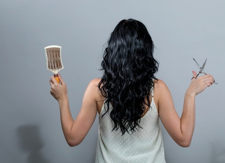 Woman cutting her hair with scissors on a gray background 写真素材