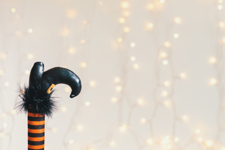 Halloween theme with witches leg decoration on a shiny light background