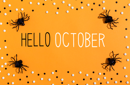 Hello October message with spiders overhead view on a solid color Stock Photo