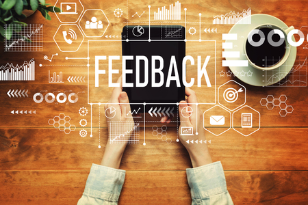 Feedback with a person holding a tablet computer Stock Photo