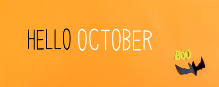 Hello October message with paper bat overhead view on a solid color