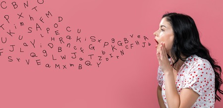 Alphabet letters with young woman speaking on a pink background