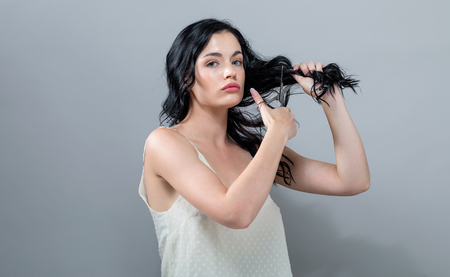 Woman cutting her hair with scissors on a gray background Stock Photo