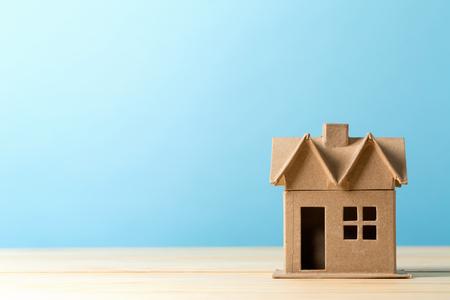 Mini casa de artesanía residencial sobre un fondo azul.