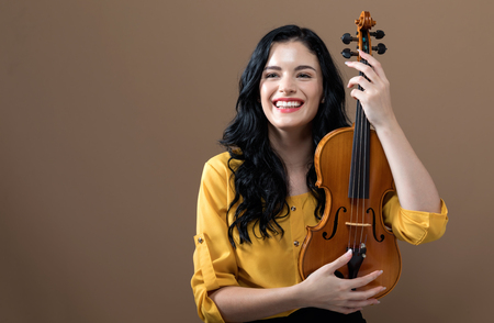 Young woman with a violin on a brown background