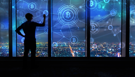 Bitcoin with man writing on large windows high above a sprawling city at night