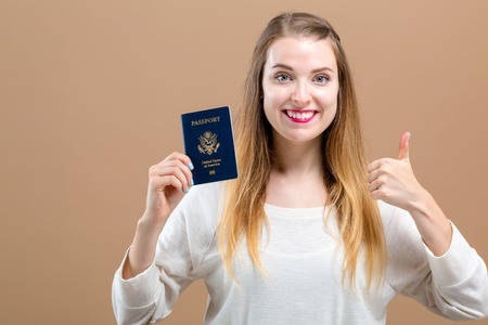 Young woman with US passport travel theme on a brown background