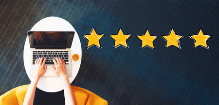 Five Star Rating with person using a laptop on a white table Banco de Imagens