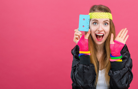Woman in 1980s fashion holding a cassette tape on a pink background