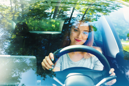 Young woman driving a new luxury car Stock Photo