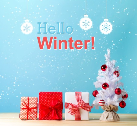 Hello winter message with a white Christmas tree and gift boxes