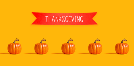 Thanksgiving message with orange pumpkins with a red banner