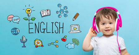 English with toddler boy with headphones on a blue background Stock Photo