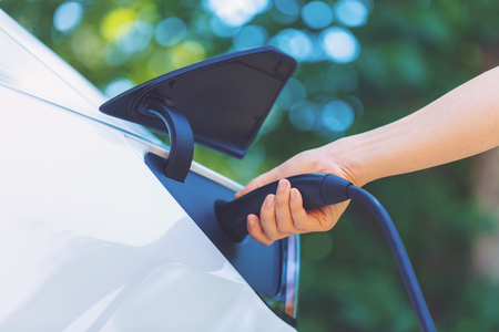 Person charging an electric vehicle with green background
