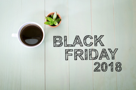 Black Friday 2015 text with a cup of coffee on pastel green wooden table