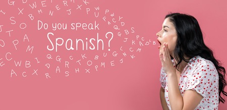 Do you speak Spanish theme with young woman speaking on a pink background Archivio Fotografico