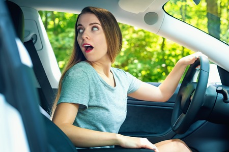 Young woman backing up in a new luxury car Stock Photo