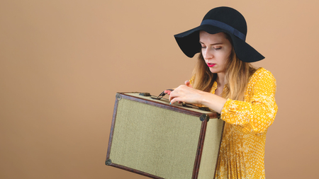 Young woman with a suitcase travel theme on a brown background Reklamní fotografie - 109559461