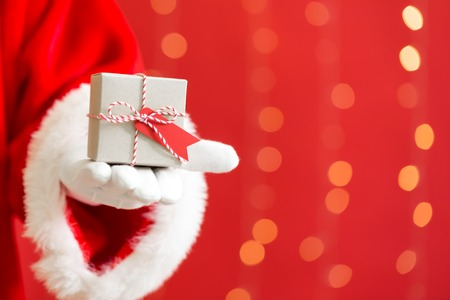 Santa holding a small Christmas gift on a shiny light red background
