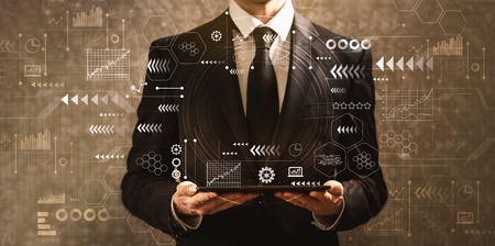 Technology screen with grid with businessman holding a tablet computer on a dark vintage background Stock Photo