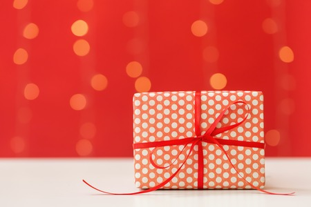 Christmas gift box on a shiny light red background