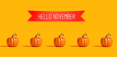 Hello November with orange pumpkins with a red banner Stock Photo