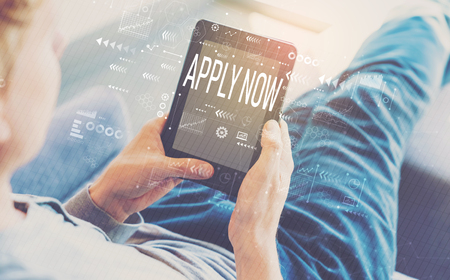 Apply now with man using a tablet in a chair Stock Photo