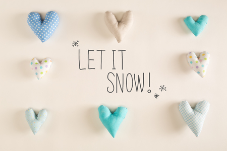 Let It Snow message with blue heart cushions on a white paper background Фото со стока