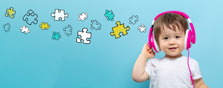 Puzzle pieces with toddler boy with headphones on a blue background