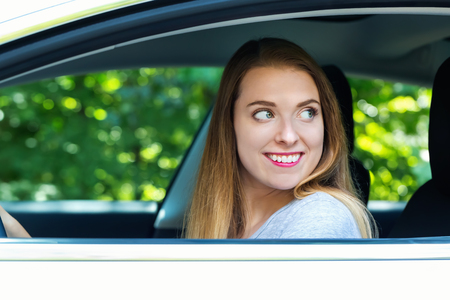 Happy young woman in a new luxury car Stock Photo