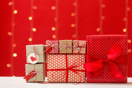 Christmas gift boxes on a shiny light red background