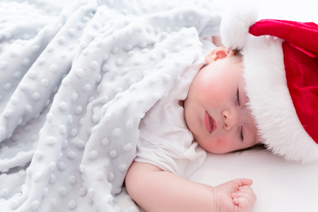 Toddler boy sleeping with a Santa hat around Christmas time Stock Photo