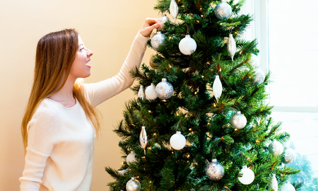 Happy young woman decorating her Christmas tree in her house Banque d'images