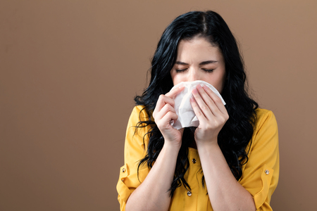 Sick young woman with tissues on a brown background
