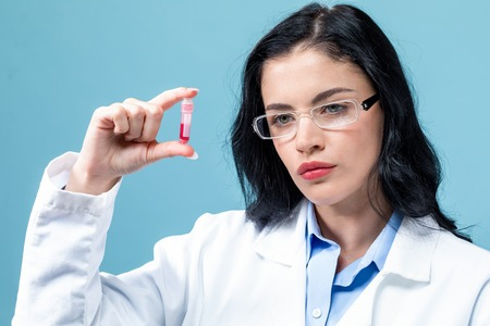 Laboratory scientist researcher with a test vial on a blue background