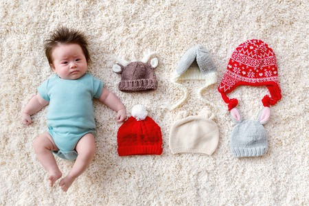 Newborn baby boy with assorted baby knitted hats Фото со стока