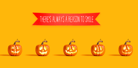 There is always a reason to smile with orange pumpkin lanterns with a red banner Фото со стока