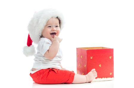 Heureux petit garçon avec un bonnet de Noel avec une boîte de cadeau de Noël