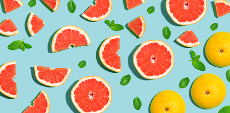 Halved fresh grapefruits on bright color background 스톡 콘텐츠