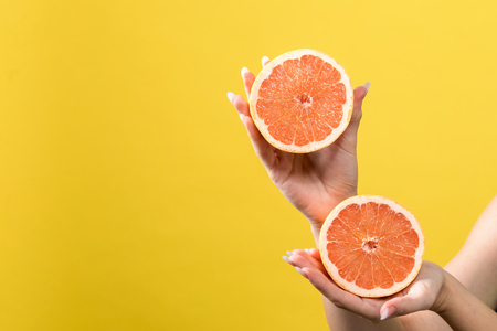 Young woman holding oranges on a yellow background