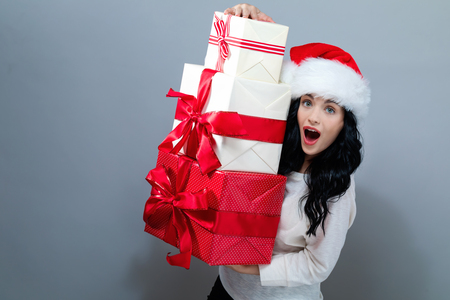 Young woman with santa hat holding gift boxes on a gray background Stok Fotoğraf
